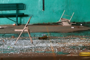 Chairs, glass, debris, and water lay on the ground inside the MLK Center gym. By Philip Hall, Enterprise-Journal.